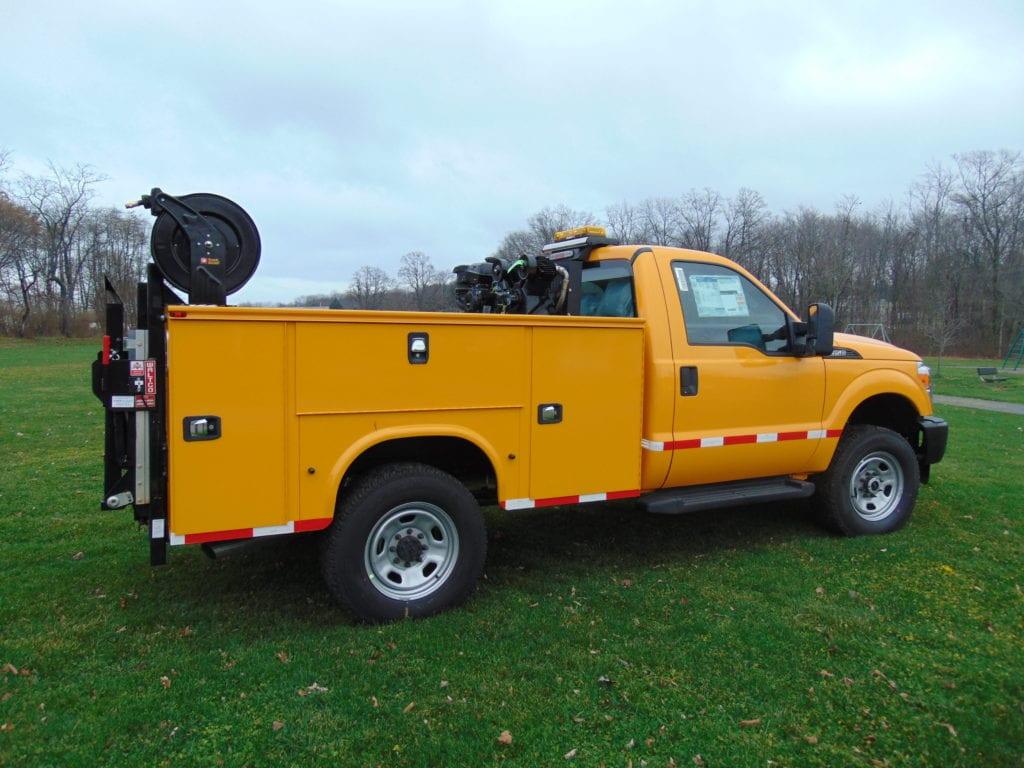 yellow work truck parked in grass field