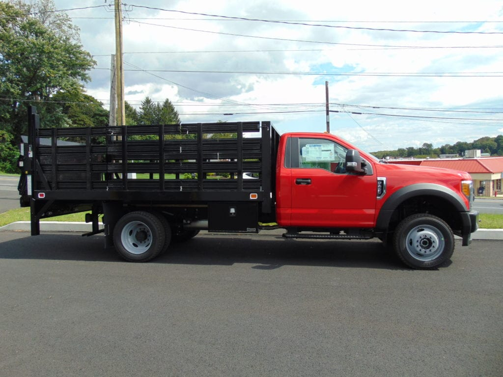 side of red and black flatbed truck parked on pavement