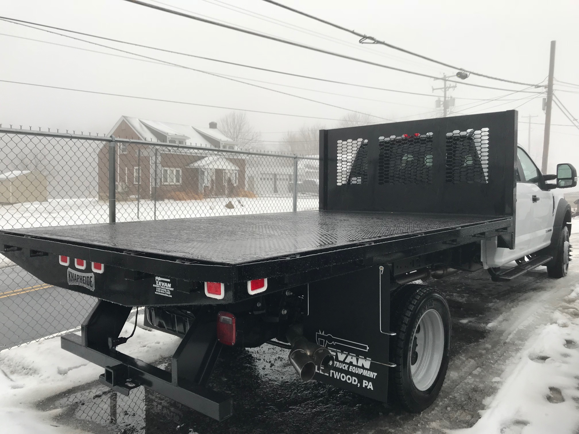 back of black and white flatbed truck parked in snow