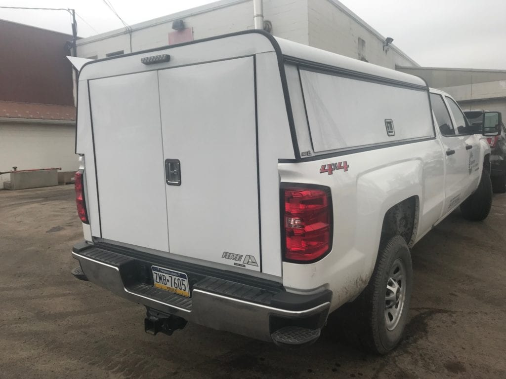 cover on back of white pickup truck