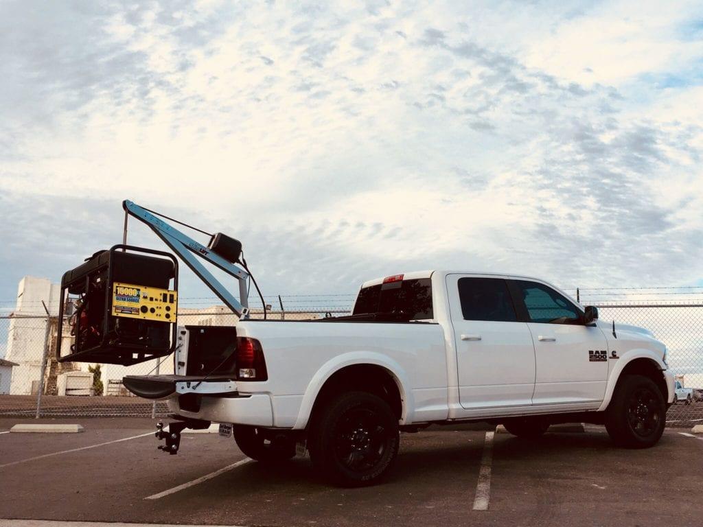 back of white pickup truck hoisting generator